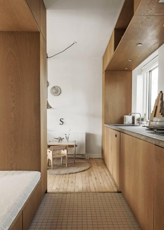I stedet for å la kjøkken og stue smelte helt sammen, kan du lage en praktisk romdeler som fungerer som både skap og sitteplass. Kombinasjonen av åpne og lukkede elementer både skiller og samler de to rommene. Tips! Har du en liten bolig, er oppbevaringsplass svært viktig. Gjem vekk nips og kjøkkenting i skap og skuffer, så blir uttrykket rent. Har du mange ting stående på bord og hyller, vil rommet virke mindre. FOTO: Peter Kragballe