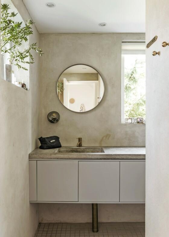 De pussede veggene og betongbordplaten gir et rått stilpreg på badet. Tips! Bruker du tøffe materialer som betong, bør du myke opp uttrykket for eksempel med armaturer av messing. FOTO: Peter Kragballe