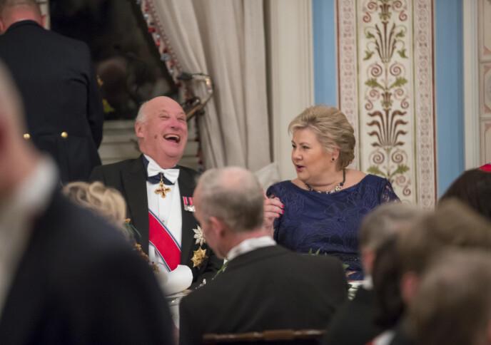 TOK DET MED ET SMIL: Kong Harald og statsminister Erna Solberg under den tradisjonsrike stortingsmiddagen på Slottet. Kanskje var det NTBs blemme kongen lo av? FOTO: Heiko Junge/NTB