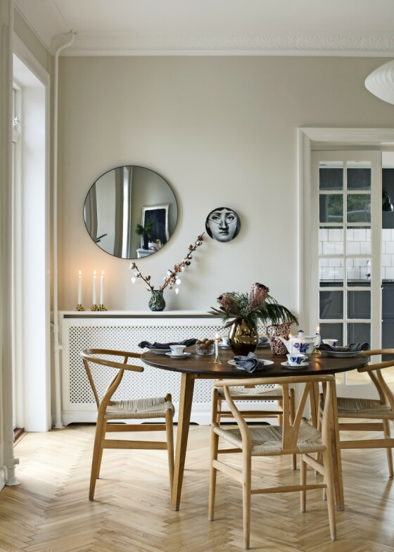 Ved å male veggene i avdempede farger i stedet for det klassiske hvite, kan du fort gi hjemmet ditt en varm og hyggelig atmosfære som kommer til sin rett spesielt i den mørke årstiden. Stolene er designet av Wegner, lysestakene på radiatorskjuleren er fra Gejst, og gullvasen fra Kähler. Tips! Klassisk, moderne design, som for eksempel Wegner-stoler, passer i nesten alle slags rom – dette er 120 år gammelt. FOTO: Kira Brandt
