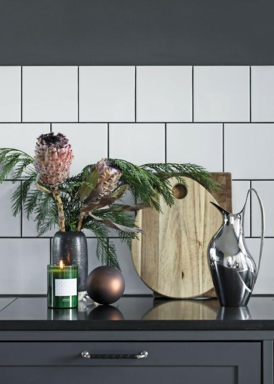 Det kan være vanskelig å pynte kjøkkenet, fordi det praktiske og hygieniske ofte kommer i første rekke. Men det skal ikke mer til enn en bukett med granbar og kanskje et par enkle pynteting, så er også kjøkkenet klart for jul. Og levende lys skaper alltid stemning. Duftlyset er fra Ferm Living, muggen fra Georg Jensen. FOTO: Kira Brandt