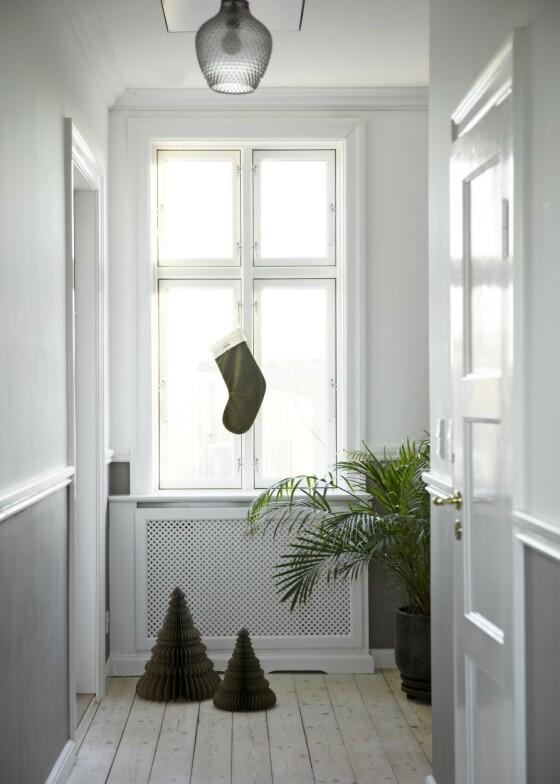 Tradisjonen med å henge opp en julesokk skal ha begynt allerede i vikingtiden, da barna i Danmark stilte støvlene sine fylt med gulrøtter eller halm i nærheten av pipehullet for at Odins flygende hest, Sleipner, kunne spise av dem. Christina og mannen hennes har hengt opp sokker i huset fra 1900, som paret selv har totalrenovert. Tips! Høyt under taket og vakre, klassiske detaljer. Et slikt rom er et smykke i seg selv, og trenger ikke mye pynt. FOTO: Kira Brandt