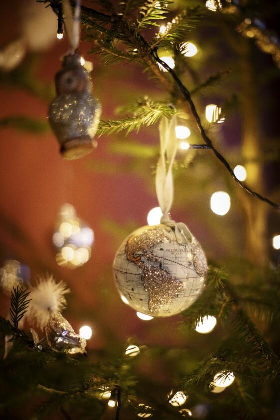 Denne vakre, glitrende globuskulen henger på et av husets ti juletrær. FOTO: Kristina Meyn Krogvold