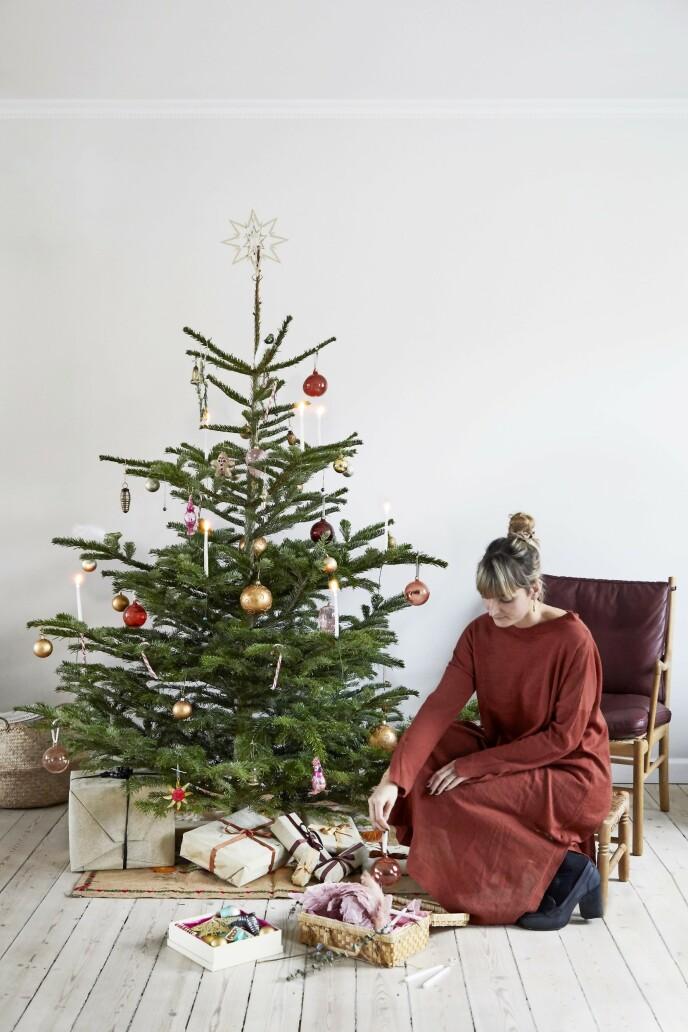 Gjør som Josefine, og pynt treet allerede i begynnelsen av desember, så det sprer god julestemning hele måneden. Juletrepynten hennes er en blanding av antikke kuler kjøpt på loppemarkeder og ny pynt fra Søstrene Grene, Flying Tiger og Iittala. Stjernen og lysholderne er fra Georg Jensen. Lenestolen er tegnet av Ole Wanscher og er fra Carl Hansen & Søn. Tips! Hvis du vil ha treet stående i hele desember, kan du plante det i en stor potte med jord, så holder det lenger.