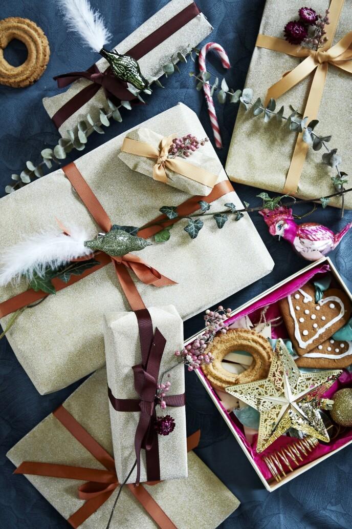 Josefine pynter sine pakker med småkaker, små dekorfugler og grønt. Båndet er fra Bungalow, og papiret er fra Flying Tiger.