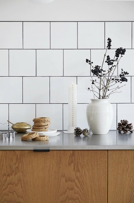 På kjøkkenet pynter Josefine opp med greiner i vaser. Vasen er fra Le Creuset, de hvite tallerkenene er håndlaget keramikk fra Robynn Storgaard, og sukkerskålen i messing er fra Tom Dixon.