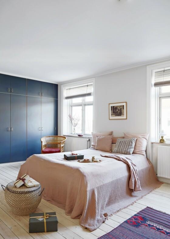 Selv om det er mer farge på soverommet, har Josefine klart å gi rommet en rolig atmosfære med støvete nyanser som den rosa fargen på sengeteppet og den kjølige blåfargen på skapveggen. Kelimteppet og puten med lilla mønster er fra en reise til Jordan, kurvene på gulvet er fra Kurvebutikken i Valby, og puter og sengetepper er sydd på mål til sengen.