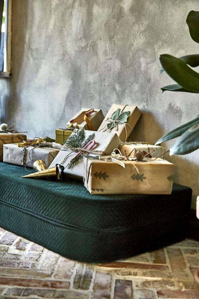 De første julegavene er blitt pakket inn i gavepapirrester og gammelt papir som blir brukt på nytt. Også er de blitt pyntet med små, dekorative kvister fra hagen. FOTO: Lene Samsø