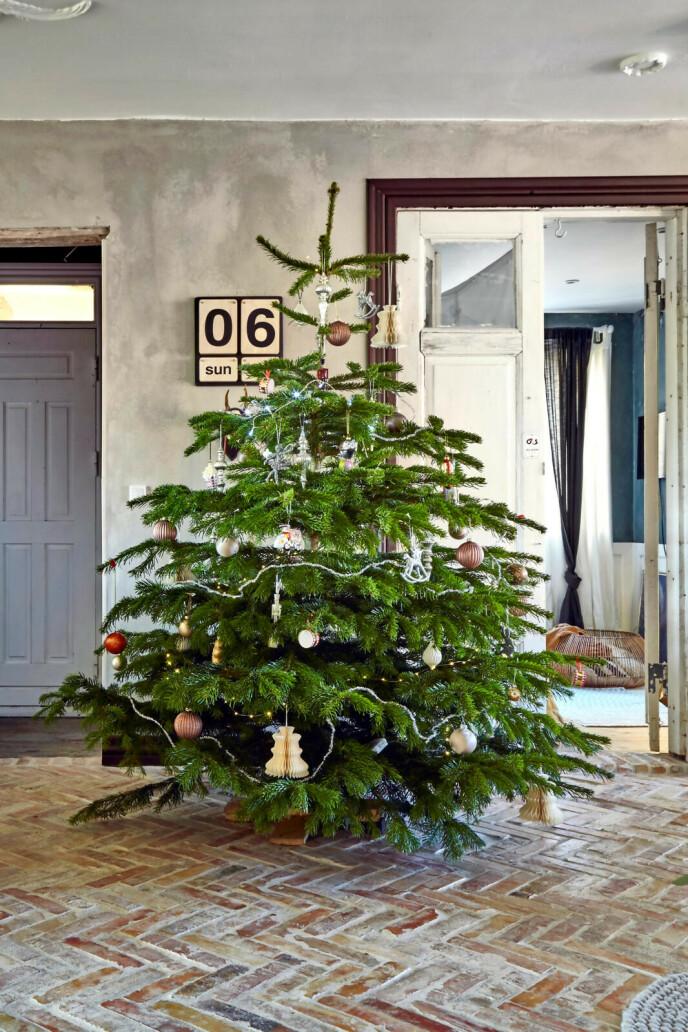 Juletreet står framme hele desember og blir pyntet etter hvert som pynten blir funnet fram – eller laget. Den er en blanding av nytt, gammelt, hjemmelaget og fine julekuler som barna elsker. Tips! Grove materialer som mur og treverk er hovedingrediensene i en rustikk stil som dette. FOTO: Lene Samsø