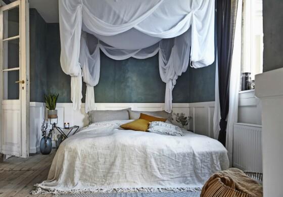 Veggen på soverommet er malt med en blå kalkfarge som er med på å understreke den rustikke stilen. FOTO: Lene Samsø