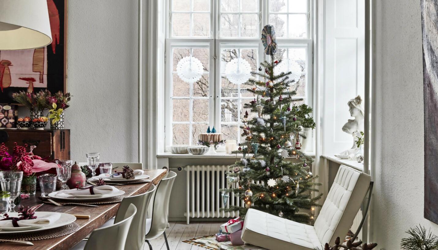 Bordet er antikt og kjøpt i Frankrike. Stolene rundt heter «Catifa» og er fra Casa Shop. Det lave, brede bordet ved veggen er et gammelt bønnebord fra Kyoto i Japan, og den hvite lenestolen i skinn er Mies van der Rohes «Barcelona»-stol. Tips! Heng store, hvite papirsnøfnugg i vinduet hvis du vil ha pynt som er både enkel og virkningsfull. FOTO: Birgitta Wolfgang