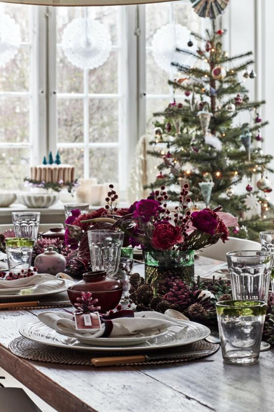 Gå for én enkelt farge eller to i alt fra pynt til julegaver og borddekking – som her, der det røde og rosa er sentralt. Fargene går igjen på servietter, tallerkener, kongler og blomster. Tips! Er det en gang i året det er helt i orden å mene at «more is more», er det når du pynter til jul. Passer det din stil og smak, så fyll opp med vakre dekorasjoner til høytiden.
