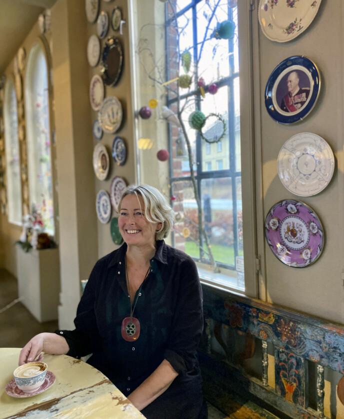 BESTEFAR PÅ VEGGEN: Benedikte Ferner har samlet inn over 300 tallerkener med motiver av forskjellige medlemmer fra den norske kongefamilien - som er hennes egen slekt. På veggen bak henne henger bestefar Olav. FOTO: Lasse Engeland