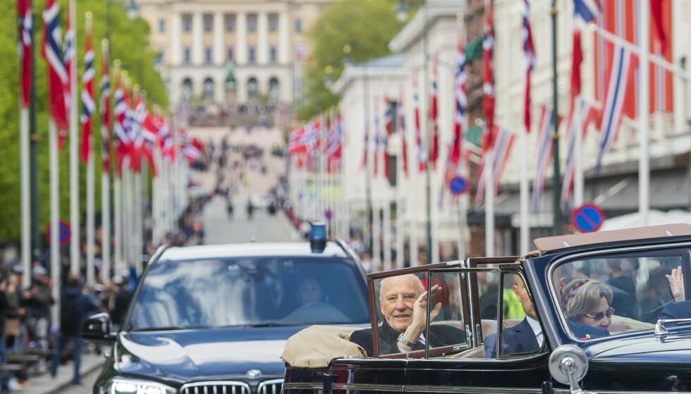 ET SYN VI ALDRI KOMMER TIL Å GLEMME: Kong Harald og dronning Sonja kjørende nedover Karl Johans gate i åpen bil under 17. mai-feiringen i Oslo. I 2020 ble nasjonaldagen feiret på en helt ny og annerledes måte på grunn av koronoaviruset - noe kongefamilien også var delaktig i. FOTO: Fredrik Varfjell / NTB