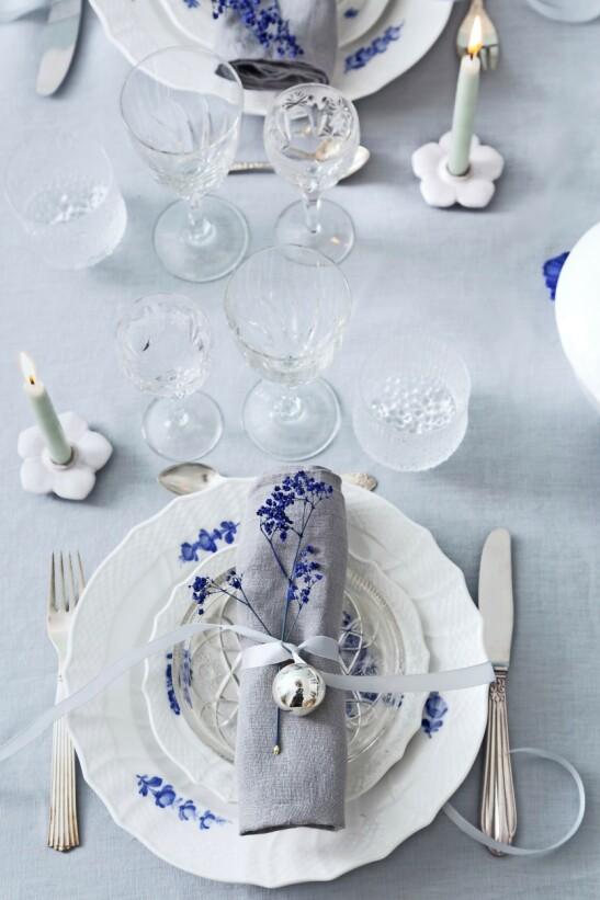 Tallerken på tallerken ser alltid festlig ut, og med et silkebånd, en kule og en enkelt blomst kan du enkelt pynte hver kuvert. Serviset er det tradisjonelle danske «Blå Blomst» fra Royal Copenhagen. FOTO: Anitta Behrendt