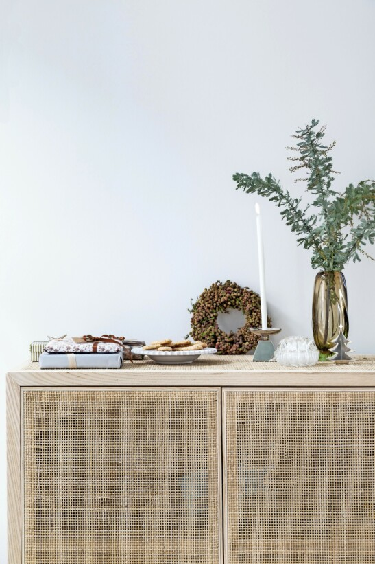 Bruk innpakkede gaver som en del av pynten. Det gir stemning, og forventningene stiger! Messingjuletre og lysestake fra dba.dk, vintagevasen er fra Brussel. Skapet er fra Ikea. FOTO: Anitta Behrendt