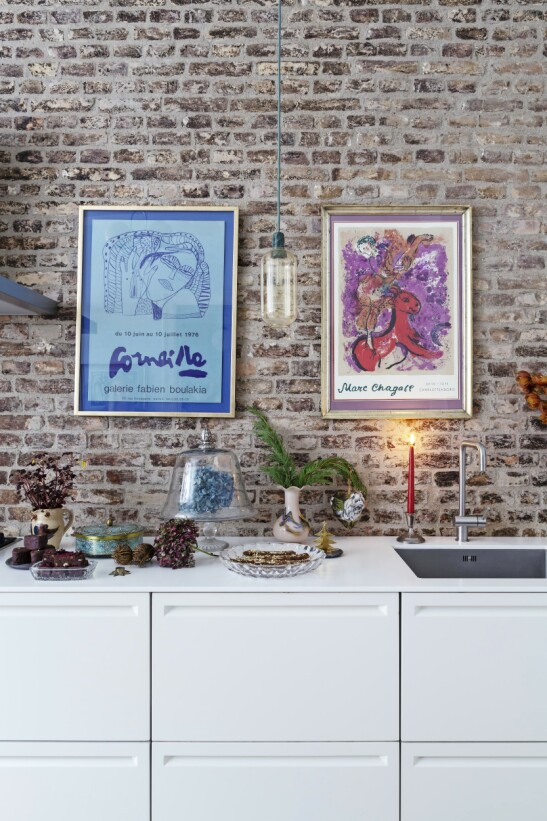 Ett enkelt rødt stearinlys hinter til den tradisjonelle julepyntingen sammen med litt grønt bar mot den vakre, rustikke veggen. Tips! Finn fram dine fineste arveting og bruktkupp fra skapet, og la dem være en del av julepynten som et lite stilleben sammen med blomster og godteri på kjøkkenbenken. FOTO: Anitta Behrendt