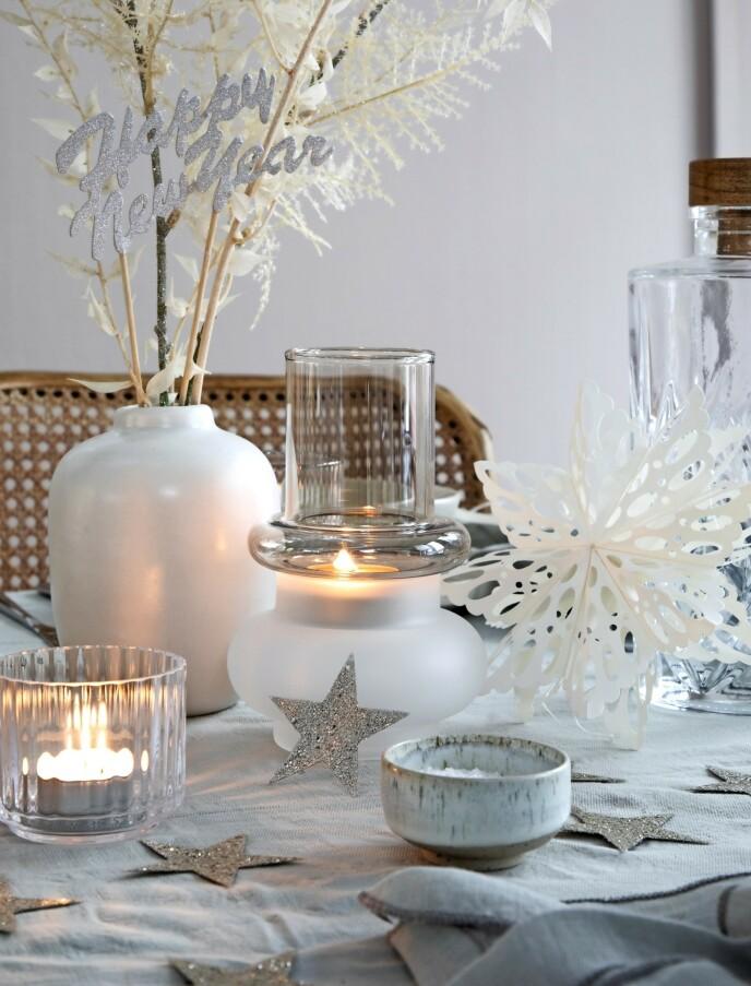 Hvit vase (Notre Dame), telysestaker i flerfarget glass, (Hübsch), liten bolle (Studio Arhoj). Liten telysestake i glass (Lyngby Porcelæn), glitterstjerner (Notre Dame), hvit papirstjerne (Notre Dame). Happy New Year-skilt på pinne (Søstrene Grene). FOTO: Pernille Enoch