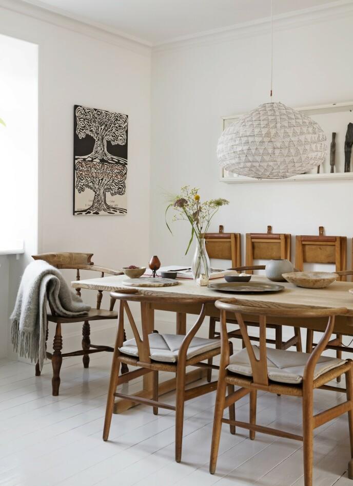 Møbelklassikere i solide materialer gjør at et møbel lett kan leve videre når det skifter eier. Børge Mogensens «Shakerbord» og Wegners «Y-stoler» er arvet, og her er de plassert i kombinasjon med loppefunn og keramikk. Over bordet henger en lampe fra Pars Au Mois D'août. Tips! Tremøbler som har rukket å få patina fra mange års bruk, skaper varme i et rom selv om det ellers tilsynelatende er hvitt og kaldt. FOTO: Kira Brandt