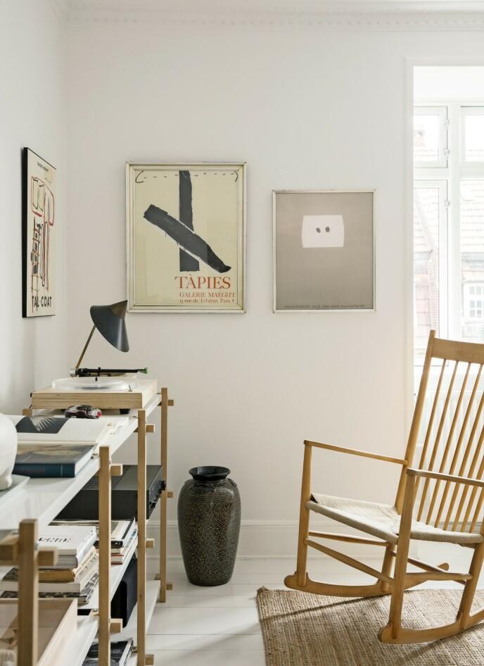I 1944 designet Wegner gyngestolen «J16», som hos Louise er akkompagnert av reolen «Woody» fra Hay. De to store møblene er begge i lyst tre, noe som gir et rolig preg. På veggene henger en miks av funn fra DBA, Danmarks svar på Finn, og plakater fra Stilleben, som tar opp fargen fra gulvvasen og bordlampen. Tips! Mellomstore interiørdetaljer som denne vasen kan gjerne stå på gulvet i stedet for å ta opp plassen på et bord eller en hylle. Da synes de bedre også. FOTO: Kira Brandt