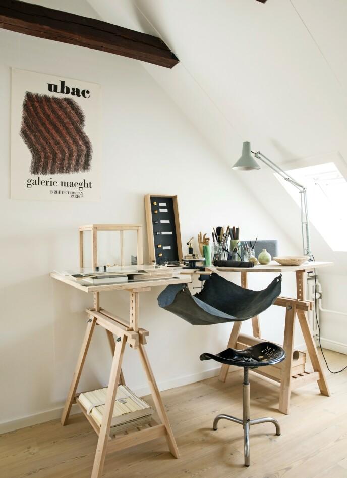 Hvis det er for lite plass til at du kan bruke et helt rom til arbeidsrom, kan du lage en arbeidskrok som går i ett med rommets øvrige innredning. Her er lyse bordbein fra Ikea og en plate av kryssfiner blitt til et bord. Krakken er et traktorsete med bein som er kjøpt på et loppemarked i Frankrike. FOTO: Kira Brandt