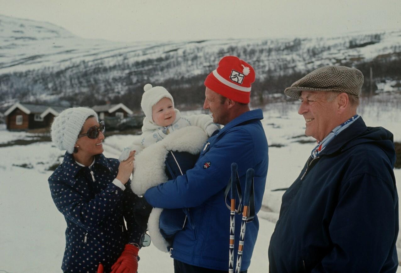 FIN FAMILIE: Året er 1974, og kongefamilien er på påskeferie i Sikkilsdalen. Kronprins Harald med prins Haakon på armen. Kong Olav er strålende fornøyd. FOTO: Svein Hammerstad / NTB