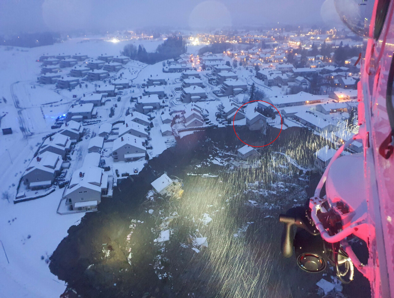 PÅ KANTEN AV SKREDET: Dette bildet er tatt fra et redningshelikopter 30. desember 2020. Den røde ringen markerer huset til familien Gulbrandsen/Brenden, som ble tatt av skredet noen timer senere. FOTO: Stringer/ AFP / NTB