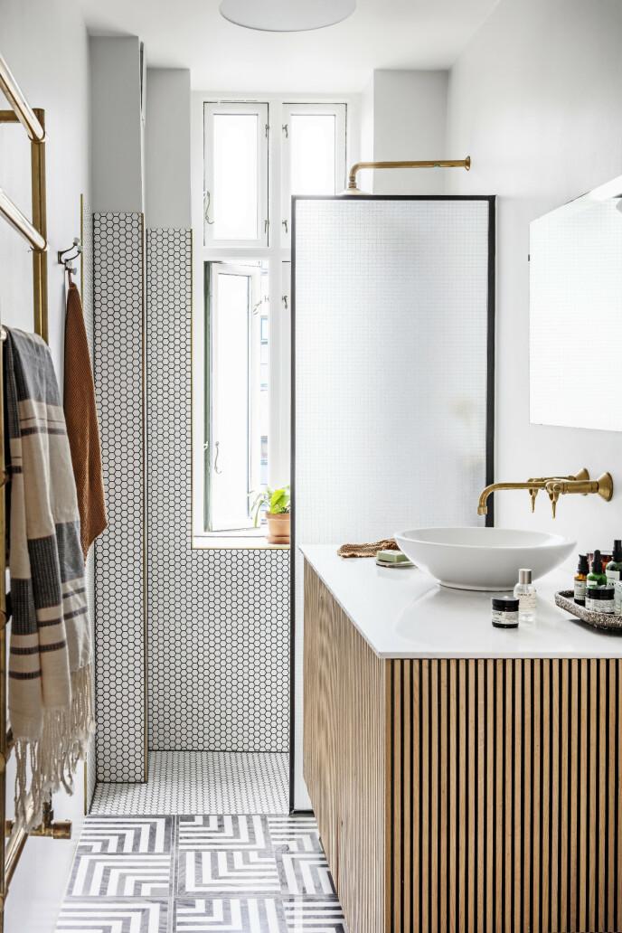 Mønsterflisene på badet er bestilt fra utlandet, og baderomsmøbelet med trelameller er bygget av en snekker. Tips! Du kan gjerne kombinere ulike mønstre på badet uten at det blir rotete å se på, hvis du bare holder deg til dempede farger og naturmaterialer. FOTO: Christina Kayser O.
