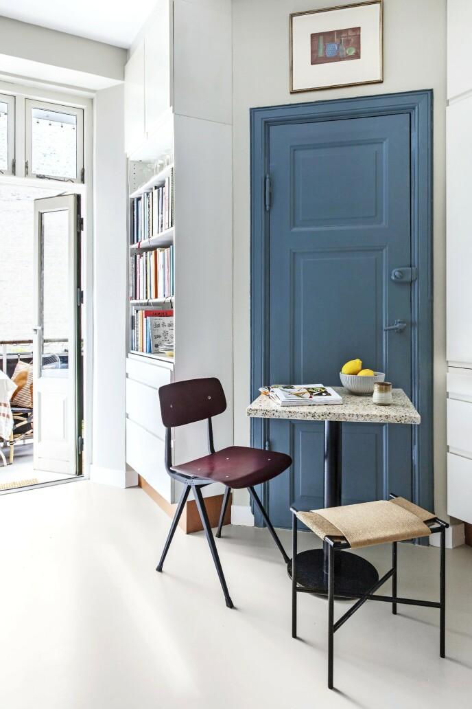 På hyllene står en stor samling kokebøker som hobbykokk Kristoffer bruker. Den røde stolen er fra Hay, krakken fra Skagerak, og bordet er laget av en gammel bordplate i terrazzo samt en ny fot. Tips! Framhev detaljer som du likevel ikke kan skjule. Her trer en dør fram i samme farge som kjøkkenveggene, selv om den er stengt av og ikke lenger har noen funksjon. FOTO: Christina Kayser O.