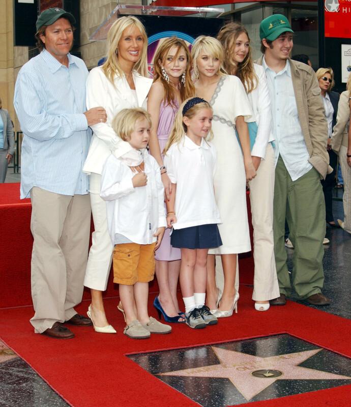I SAMLET FLOKK: Mary Kate og Ashley Olsen sammen med faren, stemoren og søsknene Elizabeth, Jake, Taylor og Trent. Fotografert i 2004, da tvillingene fikk en stjerne på Hollywood Walk of Fame. FOTO: NTB