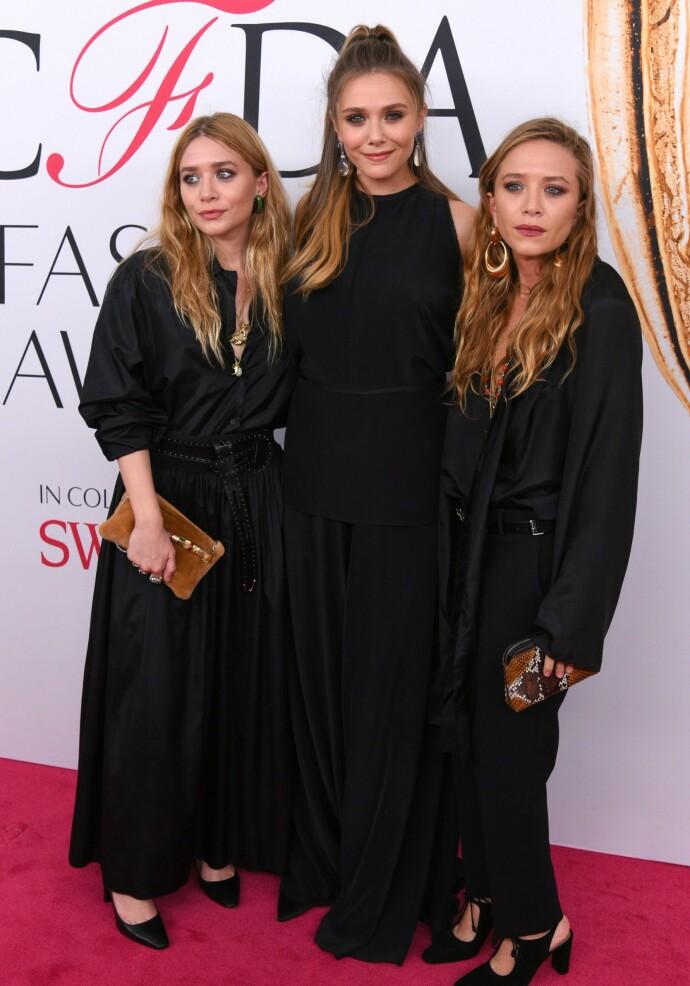 HUSET FULLT: Søstrene Mary-Kate Olsen, Elizabeth Olsen, og Ashley Olsen linet rutinert opp foran fotoveggen i 2016. FOTO: NTB