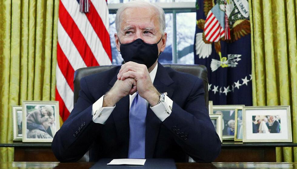 SØNNEN ER MED: President Joe Biden fotografert på det ovale kontor i Det hvite hus, etter at han tok over som president 20. januar 2020. Familiefotografiene er allerede på plass, og et bilde av Beau Biden med sin egen sønn Hunter på skuldrene, står i første rekke til venstre. FOTO: NTB