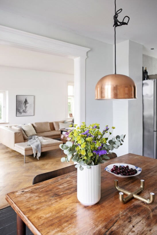 Paret har åpnet opp mellom kjøkken, spisestue og stue, og det har gitt en fin sammenheng i huset. Messingstaken er et loppefunn, og lampen er fra Menu.