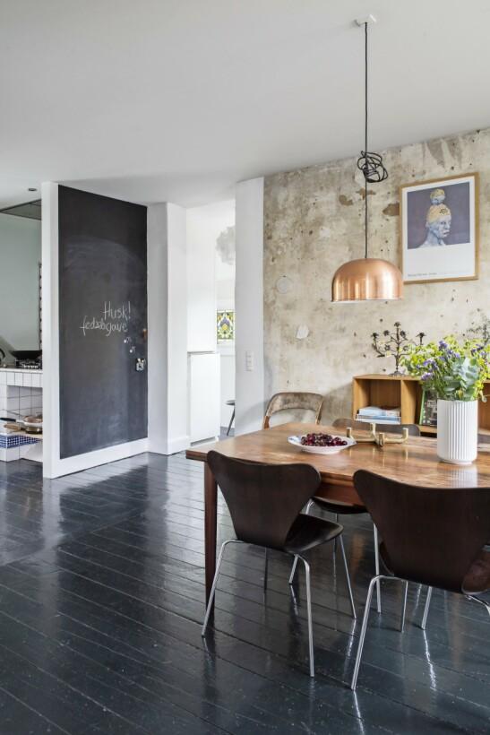 Gulvet er malt i en mørkegrønn farge med høyglans. Den lille veggen ut mot kjøkkenet har fått et par lag tavlelakk, og er nå hele familiens husketavle. Tips! Sørg for å legge like gulv der man ser gjennom flere rom. Det skaper flyt og helhet i innredningen. Her har spisestuen og kjøkken likt mørkegrønt gulv.