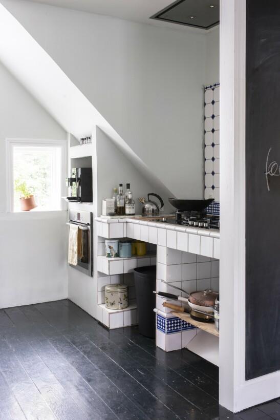 Kjøkkenet er blitt lyst og moderne med hyggelig skråtak etter Camillas og Allans renovering. Tips! Plassbygde, her flisbelagte, hyller og benker er perfekt for å utnytte plassen best mulig.