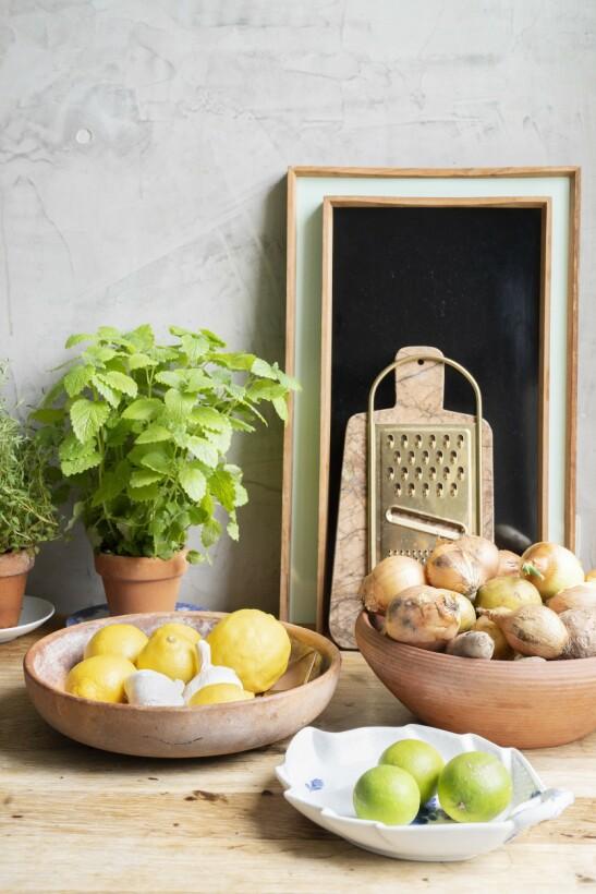 Rustikke terrakottafat i vakkert samspill med fint porselen skaper stemning på kjøkkenet.