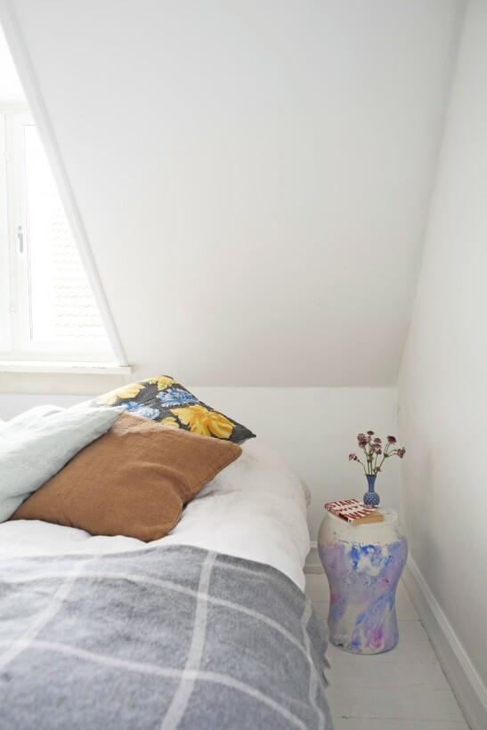 I soveværelset gir puter og nattbord farge til rommet. Bordet fikk Camilla med seg en gang hun stilte ut møblene sine i London ved siden av en kunstner med ulike designobjekter. Pledd fra Aiayu og puter fra Linum og loppemarkeder. Tips! Andre etasje i gamle hus med skråvegger er perfekte til soverom, der man ikke trenger ståhøyde i hele rommet. Man kan også plassbygge skap langs de lave veggene.