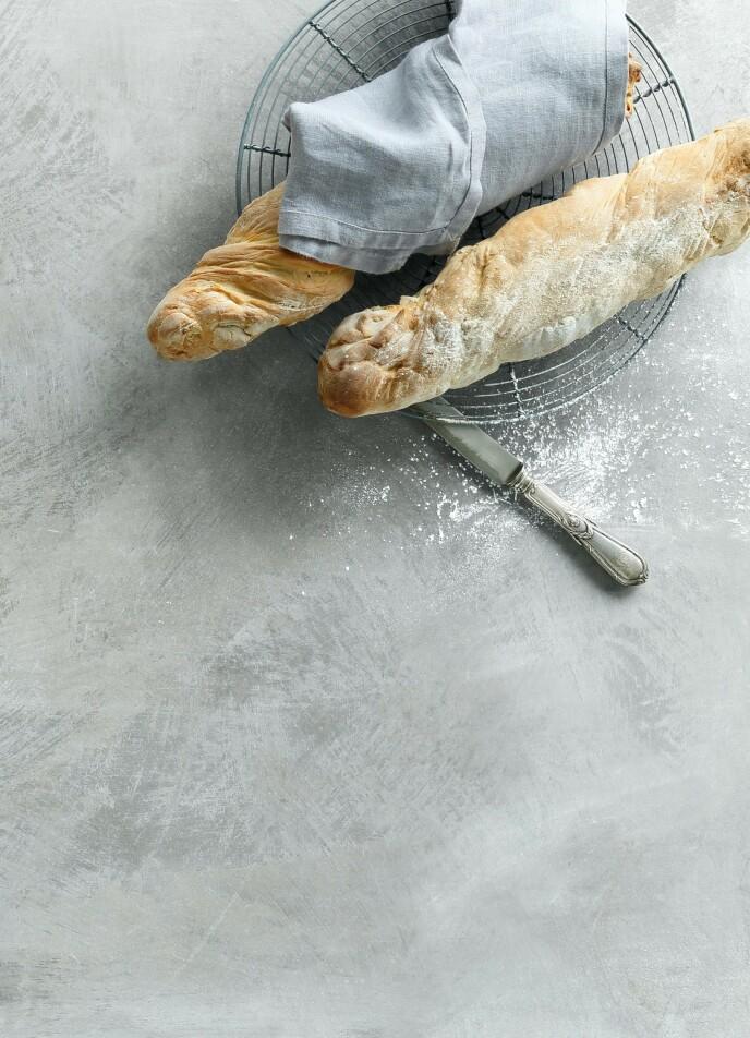 Sprø, hjemmebakte bagetter kan brukes som tilbehør til det meste. Tips! Når du vikler bagettene inn i meldryssede kjøkkenhåndklær mens de etterhever, holder de bedre den fine formen og flater ikke ut. FOTO: Martin Tanggaard