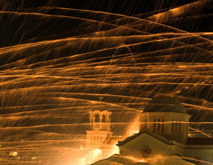 FULLTREFFER? Klokketårnet til kirken Ayios Marcos kan knapt skimtes i regnet av fyrverkeri. Målet er en innertier, rett i kirkeklokka. FOTO: NTB