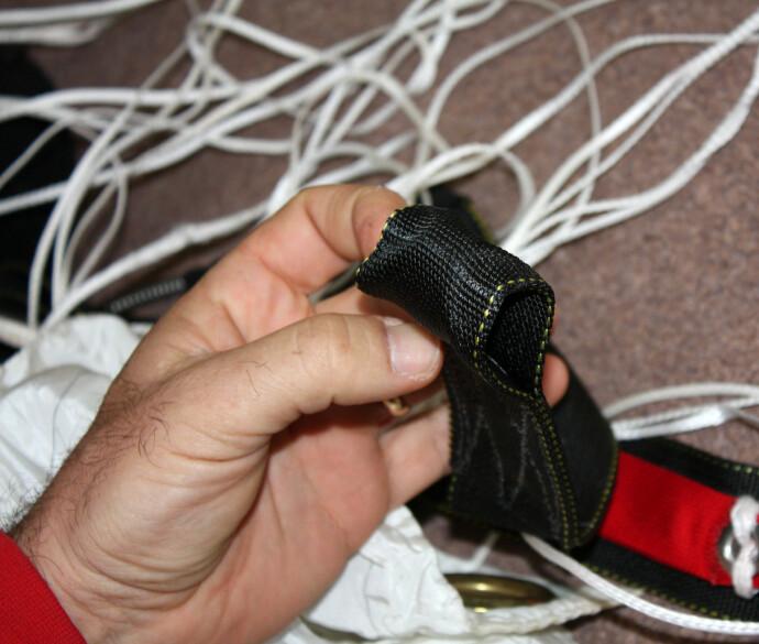 MISTENKELIG: I etterforskningen av ulykken fant man viktige deler som skulle sikre at fallskjermen løste seg ut var tuklet med. Her inspiseres stroppene på Victorias fallskjerm. FOTO: NTB
