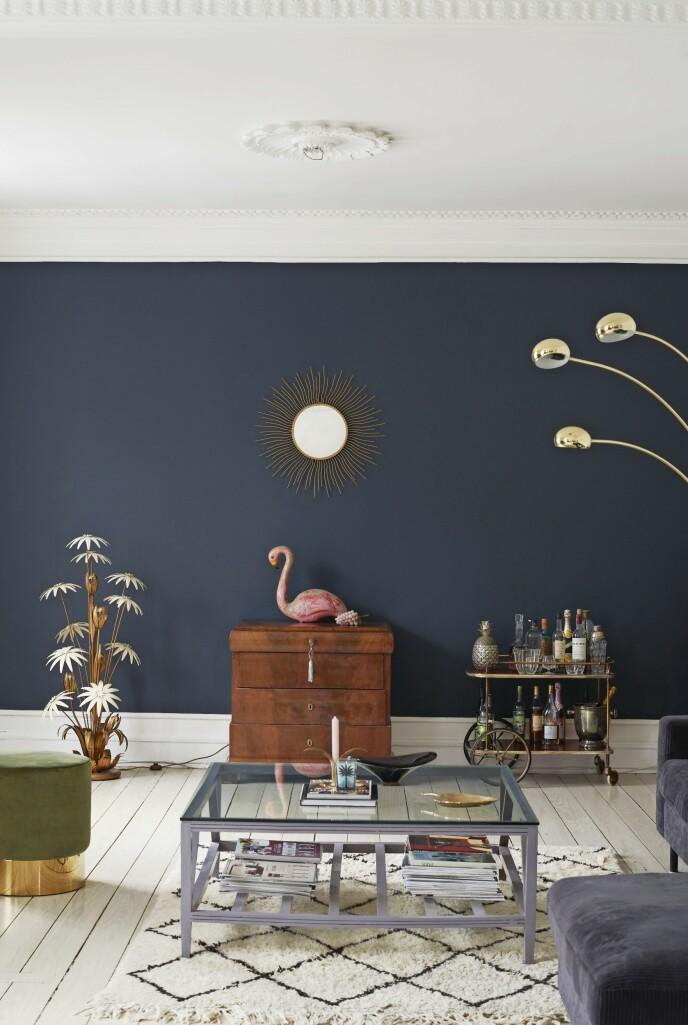 Endeveggen i stuen er malt mørkeblå. Den gir en vakker ramme omkring de gamle funnene. Veggfargen «Genève» er fra Flügger for Eilersen. Barvogn og solspeil er gamle franske ting. Sofabordet har fått ny farge med maling. Tips! Miks overdådige franske vintage-ting og moderne møbler med rene linjer.