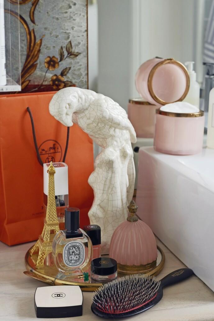 Beholderne i rosa opalglass på badet er vintage, og det er også speilbrettet og papegøyen.