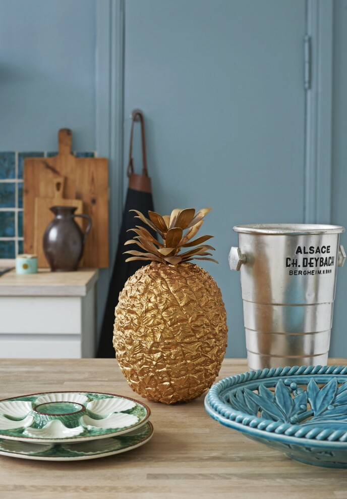 Franske vintage-detaljer som ananasisbøtten og østerstallerkenene gir liv til det enkle kjøkkenet.