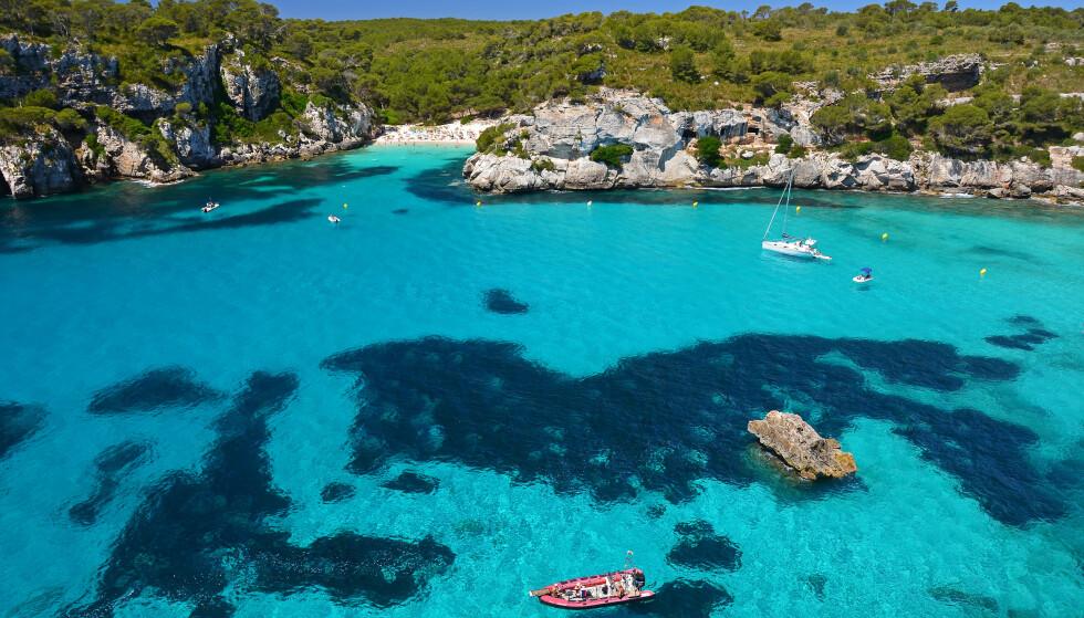 SANDRØM: De mange, fine strendene på Balearene innbyr til hverdagsleie gjester. Her er Cala Mitjana på Menorca, en liten perle som bare er cirka 25 meter bred, har den fineste myke sanden - og som ligger godt beskyttet fra store bølger. Og vannet? Krystallklart. Foto: FFTMENORCA