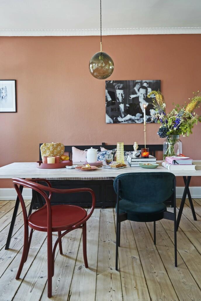 Møbler og tilbehør som er satt sammen på kryss og tvers av stilarter og perioder, gir en hyggelig og personlig stil i spisestuen. Selve spisebordet er laget av planker fra Dinesen og bordbein fra Hay. Velurstolen er fra Verpan, og den røde stolen er en gammel Ikea-stol fra @saerligtsamlet. Pendellampen er fra Missemai, og fotografiet av JFK og Frank Sinatra er funnet hos Christina Callsen. Veggen er malt med fargen Yellow Rose fra File Under