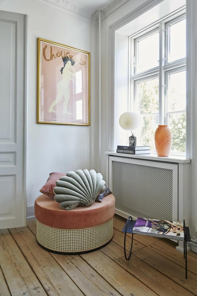 Stuens hjørner blir innredet til det fulle med både farger og former. Puffen er fra Sofacompany, og putene er fra Rêve de Renard. Plakaten er fra Beau Marché, bordlampen fra Foscarini, og vasen er funnet på etsy.com. Sidebordet er fra CasaShop