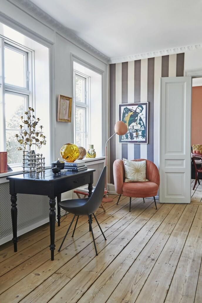 I stuen har Bettina laget seg en liten arbeidsplass med bord og stol. Stolen Dråpen av Arne Jacobsen er fra Fritz Hansen, mens glasslampen er fra Missemai. I hjørnet står en velurstol fra Sofacompany og en gulvlampe fra Gubi. Tapetet er fra Rue Verte.