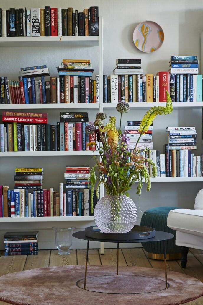 I biblioteket står to polstrede lenestoler fra Ikea med trekk sydd hos Bemz og et bord fra Beau Marché. Vasen er fra Svenskt Tenn, og platen fra veggen er designet av Stine Goya for Kähler. Teppe fra Ege.