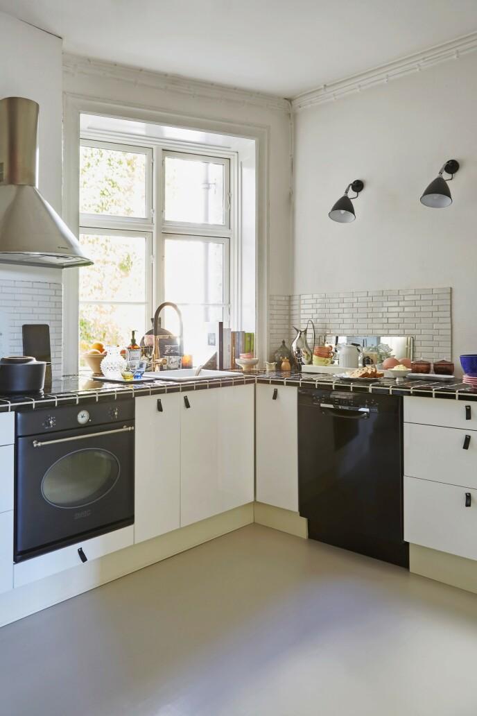 Paret har ikke så mye skapplass, og derfor står mye av kjøkkenutstyret framme og er lett tilgjengelig. Det svart-hvite kjøkkenet er fra Ikea, og er blitt tilsatt skinnhåndtak. Benkeplaten er laget av svarte fliser, mens veggen har fått hvite fliser. De to vegglampene er Bestlite fra Gubi. Armaturen er fra Dornbracht og kjøkkenvifte og komfyr fra Smeg.