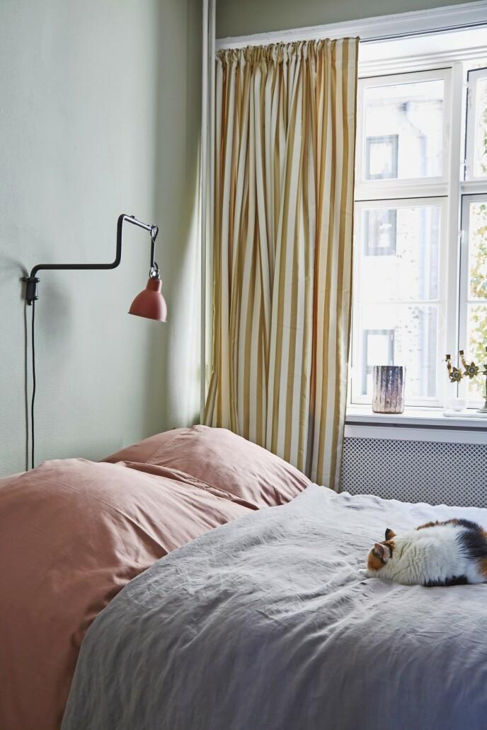 Soverommet er innredet med tunge, draperte gardiner i silkesateng fra Ellos for å skape ordentlig koselig vinterhule-stemning. Veggene er malt med den diskré fargen French Grey fra Farrow & Ball, mens vegglampen er fra Lampe Gras. Sengetøyet er fra Juna og sengeteppet fra Society